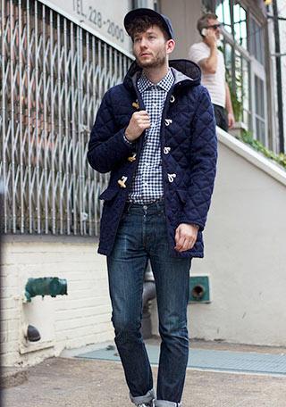 ギンガムチェックシャツやキャップを加え、よりカジュアルテイストに仕上げたフードキルティングジャケット×ジーンズの着こなし。 このままでもいいですが、シャツを