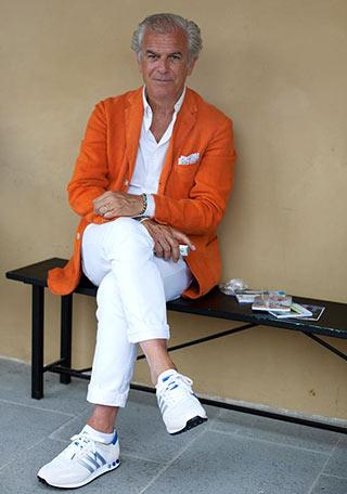 渋い60代男性だからこそ似合う、鮮やかなオレンジカラーのテーラードジャケットに白パンツを合わせた着こなし。  オレンジ色が若々しくてオシャレに映えていますね。